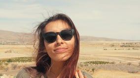 Ung attraktiv le blandad sprungen flickastående i en öken Lycklig turist- kvinna som poserar på kamera med hår som vinkar i vinde lager videofilmer