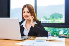 Ung attraktiv lycklig asiatisk affärskvinna som använder hennes telefon och w Royaltyfri Foto