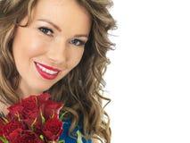 Ung attraktiv lycklig kvinna som rymmer en grupp av röda rosor Arkivfoto