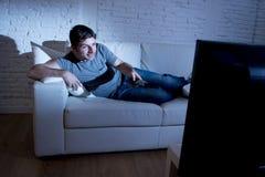 Ung attraktiv lycklig man som ligger på soffan på vardagsrum som håller ögonen på hållande fjärrkontroll för upphetsad tv Royaltyfri Foto
