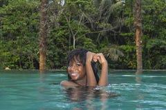 Ung attraktiv lycklig svart afrikansk amerikankvinna som tycker om ferier i tropisk semesterortoändlighetspöl till den härliga dj Arkivfoton