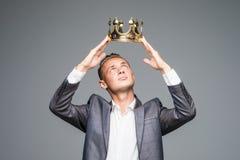 Ung attraktiv man i ett dräktinnehav ovanför hans huvud en guld- krona på en grå bakgrund royaltyfri fotografi