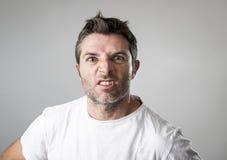 Ung attraktiv man med blåa ögon som ser ilskna och tokiga i ursinnesinnesrörelse och rubbning Royaltyfria Foton