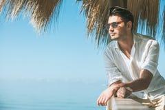 Ung attraktiv man med solglasögon som ut ser över havet under sommaren royaltyfria foton