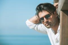Ung attraktiv man med solglasögon som ut ser över havet under sommaren royaltyfri bild