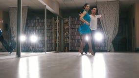 Ung attraktiv man- och kvinnadans och praktiserande latin - amerikansk dans i dräkter i studion stock video