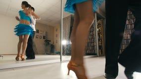 Ung attraktiv man- och kvinnadans och praktiserande latin - amerikansk dans i dräkter i studion, fokus på fot arkivfilmer