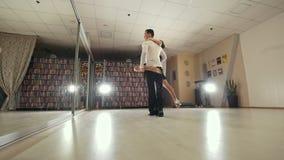 Ung attraktiv man- och kvinnadans och praktiserande latin - amerikansk dans i dräkter i studion, ultrarapid, in lager videofilmer