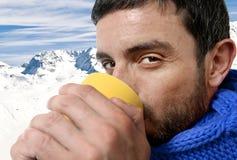 Ung attraktiv man som dricker utomhus koppen kaffe eller te i kallt vintersnöberg Royaltyfria Bilder