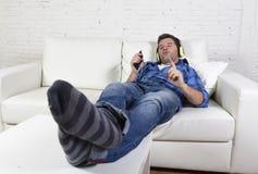 Ung attraktiv man som har roligt ensamt ligga på soffan som lyssnar till musik med mobiltelefonen och hörlurar Royaltyfri Foto