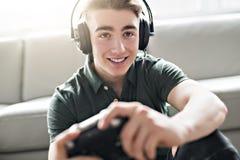 Ung attraktiv man som spelar videospel i livingroomen arkivbilder