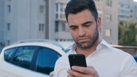 Ung attraktiv man som står på parkering nära kontorsbyggnad som skriver ett meddelande på hans Smartphone stilig aff?rsman stock video