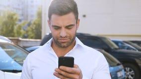 Ung attraktiv man som står på parkering nära kontorsbyggnad som skriver ett meddelande på hans Smartphone stilig aff?rsman arkivfilmer