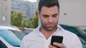 Ung attraktiv man som står på parkering nära kontorsbyggnad som skriver ett meddelande på hans Smartphone stilig aff?rsman lager videofilmer