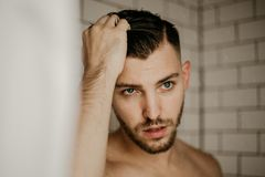 Ung attraktiv manlig modell Washing Hair i våt dusch för moderiktig modern gångtunneltegelplatta arkivfoto