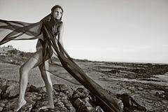 Ung attraktiv modell på stenstrand Arkivbild