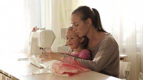 Ung attraktiv moder som arbetar på symaskinen med hennes lilla gulliga dotter lager videofilmer
