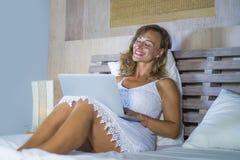 Ung attraktiv och härlig lycklig Caucasian kvinna30-tal som ligger i den hemmastadda användande internet för säng som arbetar på  royaltyfri bild