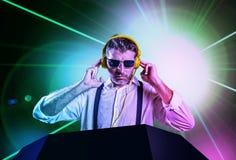Ung attraktiv och kall discjockey i skjortan och hängslen som remixing musik på nattklubben som använder hörlurar i partistro royaltyfri foto