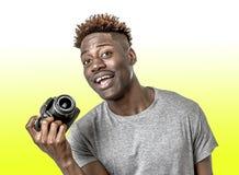 Ung attraktiv och kall lycklig svart afro amerikansk man som rymmer den digitala reflexfotokameran som ler upphetsat som isoleras fotografering för bildbyråer