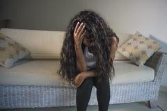 Ung attraktiv och ledsen svart afrikansk amerikankvinna som sitter deprimerade hemmastadda angelägna soffasoffakänslor och frustr arkivfoto