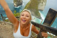 Ung attraktiv och lycklig blond turist- kvinna som tar selfie på den härliga synvinkeln för havsklippastrand som tycker om exotis royaltyfria foton