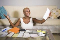 Ung attraktiv och lycklig lyckad svart afro amerikansk kvinna som in ler tillfredsställda inhemska redovisningsaffärsskatt och be Arkivbilder
