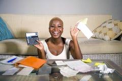 Ung attraktiv och lycklig lyckad svart afro amerikansk kvinna som in ler tillfredsställda inhemska redovisningsaffärsskatt och be Arkivfoto