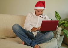 Ung attraktiv och lycklig man i den Santa Klaus Christmas hatten genom att använda bärbar datordatoren för att köpa xmas-gåvor oc arkivfoton