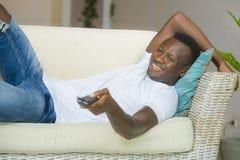 Ung attraktiv och lycklig svart afrikansk amerikanman som rymmer tycka om för film för television för avlägsen kontrollant för TV royaltyfria foton