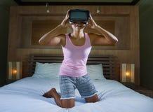 Ung attraktiv och lycklig tonårig flicka på säng som spelar med videospelet för VR-virtuell verklighetskyddsglasögon som har roli royaltyfri fotografi