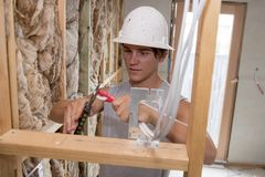 Ung attraktiv och säker byggmästare- och konstruktörjobbdeltagare i utbildning som lär att arbeta på den industriella elektriska  Arkivbild