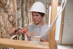 Ung attraktiv och säker byggmästare- och konstruktörjobbdeltagare i utbildning som lär att arbeta på den industriella elektriska  Royaltyfri Fotografi