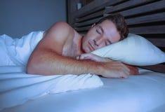 Ung attraktiv och stilig trött man på hans 30-tal eller 40-tal, i att sova för säng som är shirtless fridfullt och kopplat av på  Fotografering för Bildbyråer