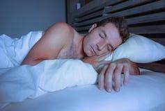 Ung attraktiv och stilig trött man på hans 30-tal eller 40-tal, i att sova för säng som är shirtless fridfullt och kopplat av på  Arkivbilder