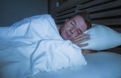 Ung attraktiv och stilig trött man på hans 30-tal eller 40-tal, i att sova för säng som fridfullt täckas med duntäcket och koppla Royaltyfria Bilder