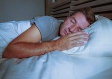 Ung attraktiv och stilig trött man på hans 30-tal eller 40-tal i säng som fridfullt sover och kopplat av på lägenhetsovrummet som Fotografering för Bildbyråer