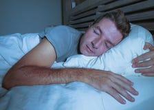 Ung attraktiv och stilig trött man på hans 30-tal eller 40-tal i säng som fridfullt sover och kopplat av på lägenhetsovrummet som Arkivbilder