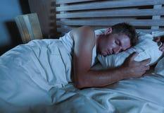 Ung attraktiv och stilig trött man på hans 30-tal eller 40-tal i säng som fridfullt sover och kopplat av på lägenhetsovrummet som Arkivfoto