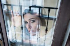 Ung attraktiv olycklig deprimerad ensam kvinna som hemma ser hopplös benägenhet på fönstret royaltyfria bilder