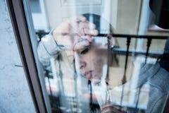 Ung attraktiv olycklig deprimerad ensam kvinna som hemma ser hopplös benägenhet på fönstret royaltyfria foton