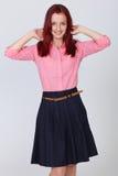 Ung attraktiv redheadkvinnlig i rosa skjorta Arkivfoton