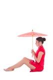 Ung attraktiv sammanträdekvinna i röd japansk klänning med umbrel Arkivbild