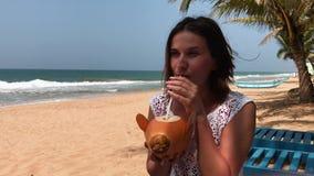 Ung attraktiv sexig kvinna på semestern som sitter vid havet, tropisk strand och att dricka coctailen i kokosnöten som in reser lager videofilmer