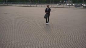 Ung attraktiv skäggig affärsman som går med hans bagage till flygplatsen lopp för timezone för tid för affärsklockabegrepp olikt  arkivfilmer