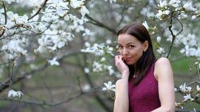 Ung attraktiv slank kvinna som poserar över att blomstra magnoliaträd och blommor på den tidiga våren som är långsam arkivfilmer