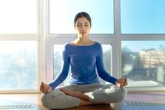 Ung attraktiv sportflickakvinna som gör yoga i morgonsolsammanträdet i den Lotus positionen på fönstret Stående i naturligt l arkivfoto