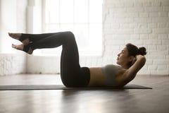 Ung attraktiv sportig kvinna som öva den Sit Ups övningen, studi Royaltyfri Bild