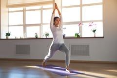 Ung attraktiv sportig kvinna som gör yoga i ett ljust soligt rum, arkivfoton