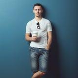Ung attraktiv stilig man i den vita t-skjortan fotografering för bildbyråer